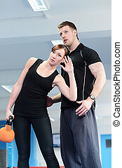 Personal trainer with female client using weights