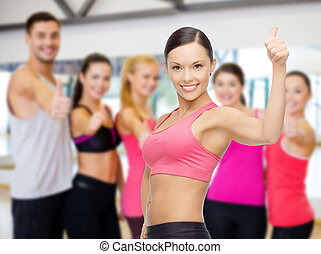 personal trainer with group in gym - fitness, sport,...