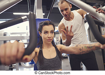 Personal trainer with woman in fitness center