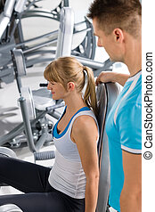 Personal trainer with young woman at gym