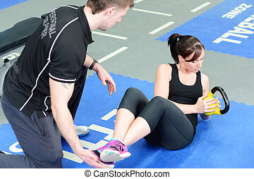Personal trainer workout - Young woman working out with...