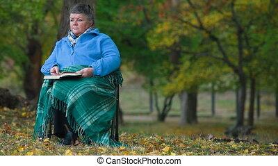 personne âgée femme, lecture, dehors