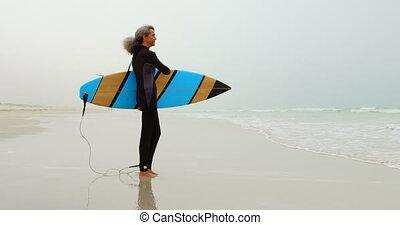 personne agee, debout, côté, africaine, actif, vue, femme, surfeur, américain, plage, planche surf, 4k