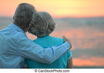 personnes âgées accouplent, à, coucher soleil