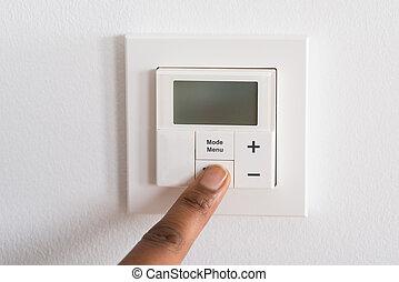 Person's Finger Adjusting Room Temperature On Digital...