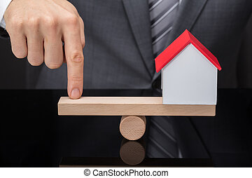 Person's Finger Balancing House Model On Seesaw