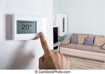 Person's Hand Adjusting Digital Thermostat - Close-up Of A...