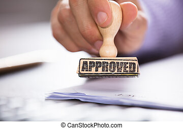 Person's Hand Holding Approved Stamp On Document