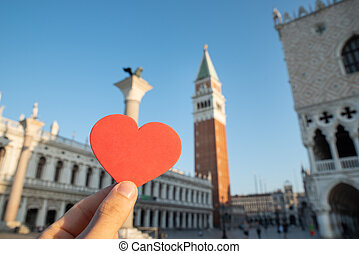 Person's Hand Holding Heart Shape In Front Of Bell Tower