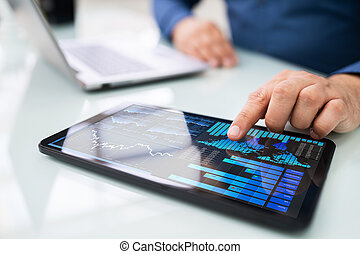 Person's Hand Pointing On Graph At Tablet
