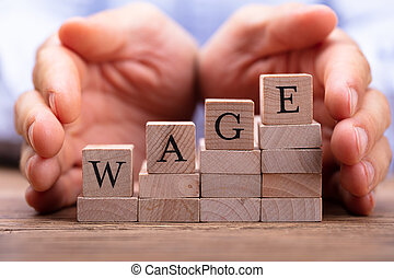 Person's Hand Protecting Wage Text On Wooden Blocks
