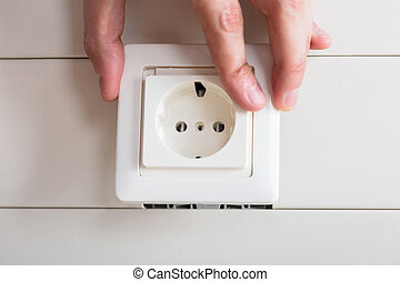 Person's Hand Repairing Electrical Socket