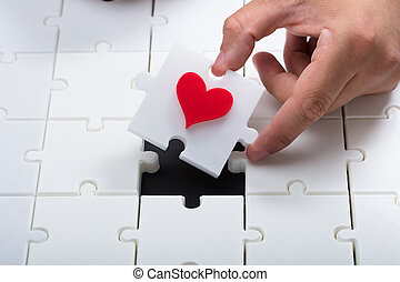 Person's hand solving white jigsaw puzzle