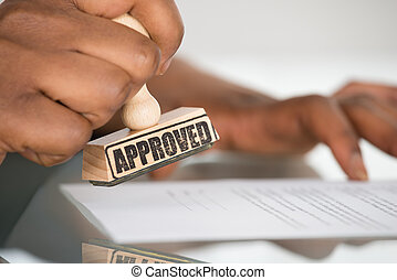 Person's Hand Stamping On Contract Form
