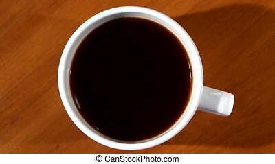 Person`s hand stir sugar in cup of black coffee, wood background