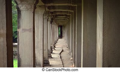 Fascinating perspective of a symmetrical, yet crumbling, outdoor corridor at the ancient ruins of Angkor Wat Temple in Cambodia.