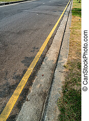 Yellow line on asphalt road with concrete curb