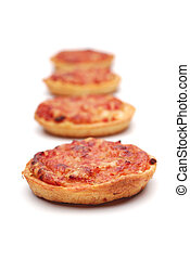 Perspective row of four fresh-baked mini-pizzas with ham and cheese.