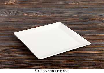 Perspective view A square plate on the white wooden table.