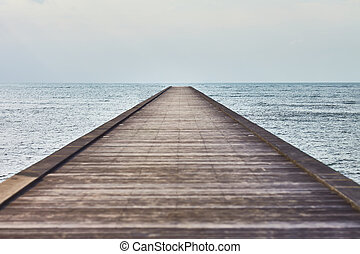 Perspective view of a wooden pier in tropical sea