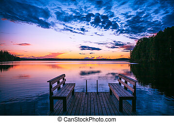 Perspective view of a wooden pier with chairs on the lake at sunset