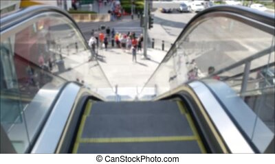Perspective view thru escalator, defocused unrecognizable group of people on road intersection crosswalk on Strip of Las Vegas, USA. Anonymous blurred pedestrians on walkway in crowded urban downtown