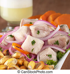 Peruvian-style ceviche made out of raw dogfish (Spanish: tollo), red onions and aji (Peruvian hot pepper) and served with roasted corn (cancha) and sweet potato with Pisco Sour (Peruvian traditional c
