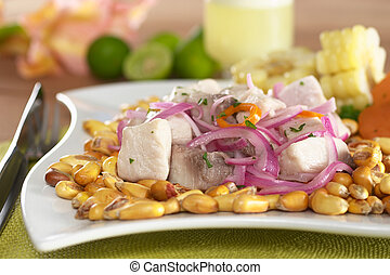 Peruvian-style ceviche made out of raw mahi-mahi fish (Spanish: perico), red onions and aji (Peruvian hot pepper) and served with roasted corn (cancha) and cooked corn. In the back Peruvian cocktail c