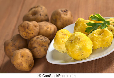 Peruvian yellow potato cooked and raw (Selective Focus, Focus on the first cooked potato)