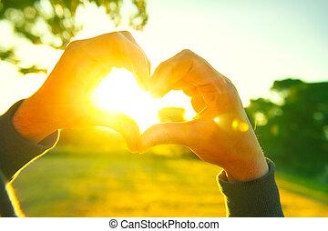 pessoa, fazer, coração, com, cedam, natureza, pôr do sol, experiência., silueta, mãos, em, forma coração, com, sol, dentro