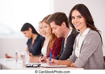 pessoas, em, a, seminar., atraente, mulher jovem, sorrindo, câmera, enquanto, sentar-se, com, outro, pessoas, tabela