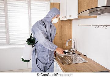 Pest Control Worker Spraying Pesticide In Kitchen - Pest...