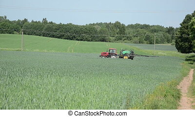 pesticides fertilizing - small red farm tractor with...