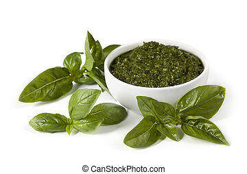 Basil pesto in a small white bowl, with fresh basil leaves. Isolated on white.