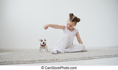 Pet and dog concept. Cute Little girl playing with a puppy at home