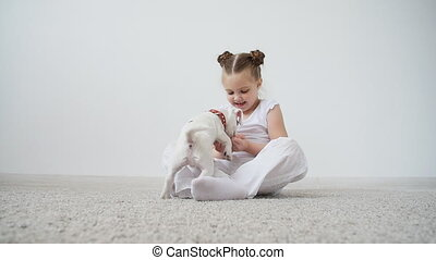 Pet concept. Cute girl playing with a dog at home in white interior