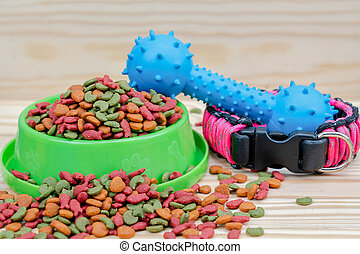 Pet food with rubber toy on wooden background