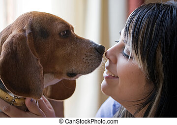 A pretty young woman posing with her beagle pup. Shallow depth of field.