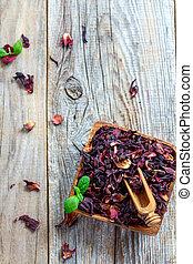 Petals Hibiscus tea in a wooden bowl.