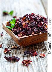Petals Hibiscus tea in the wooden bowl.