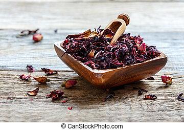 Petals of hibiscus tea in a wooden bowl.