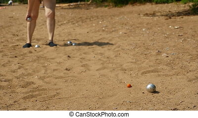 Petanque game slow motion - Petanque, person throws steel...