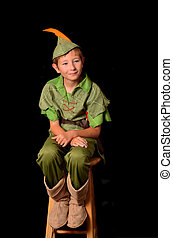 Peter Pan - Young boy dressed as Peter Pan sitting on a...