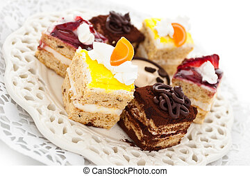 Petit fours. - Collection of different small cakes on plate....