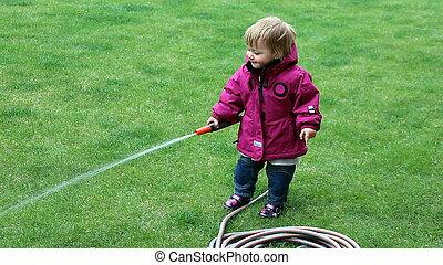 petite fille, arrosage, herbe, pelouse, dans, les, yard, à, a, tuyau
