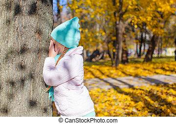 petite fille, jouant peau cycle recherche, près, arbre, dans, automne, parc