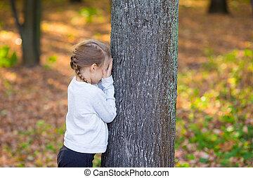 petite fille, jouant peau cycle recherche, près, les, arbre, dans, automne, parc