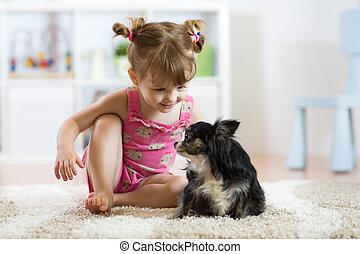 petite fille, jouer, à, elle, petit, mignon, chien, dans, les, salle de séjour
