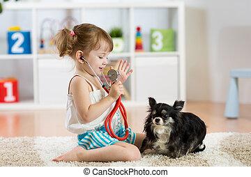 petite fille, jouer, docteur, à, elle, petit, mignon, chien, dans, les, salle de séjour