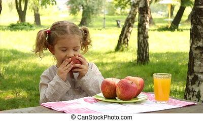 petite fille, manger, pomme, dans parc